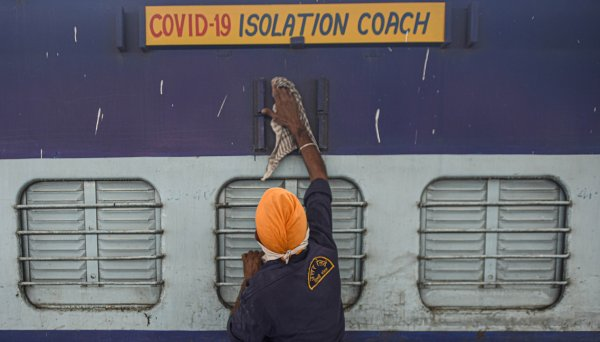 A worker cleans the exterior of a train coach that has been converted into a Covid-19 isolation ward.