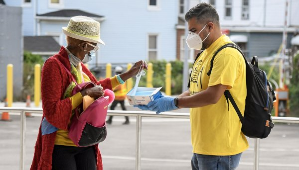 A volunteer offers a passer-by a face mask.