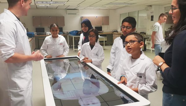 Children and scientists look at an image showing organs of the human body