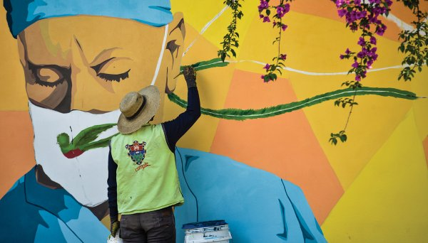 A painter paints a mural of a doctor wearing a surgical mask.