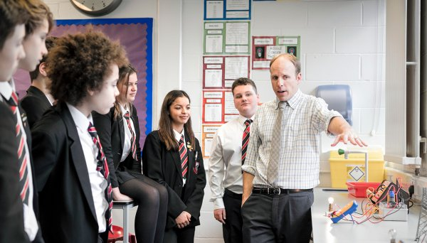 five young people and a teacher in a classroom