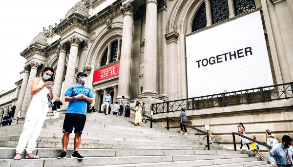 People wearing protective masks stand on the steps of the Metropolitan Museum of Art in New York which displays a banner with the word 'together'.