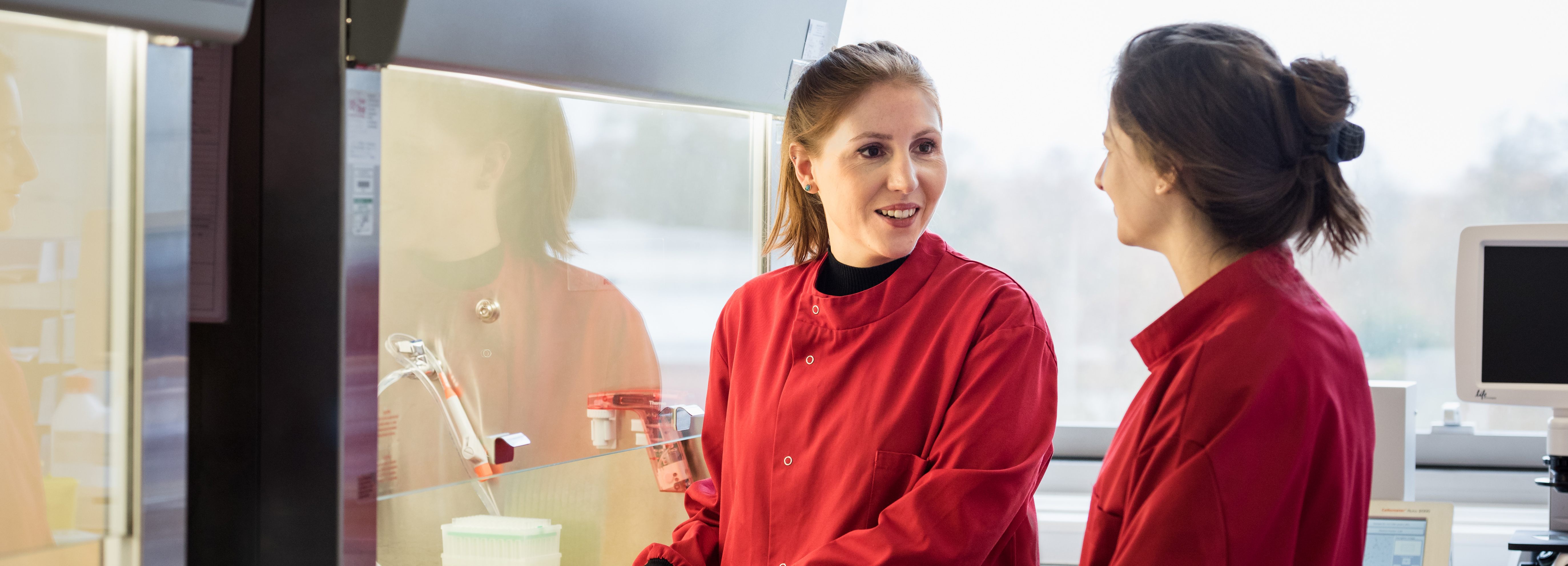 Two women wearing red lab coats talking to each other