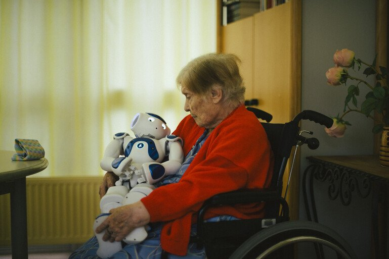 Woman in a nursing facility who has developed an emotional attachment to a robot
