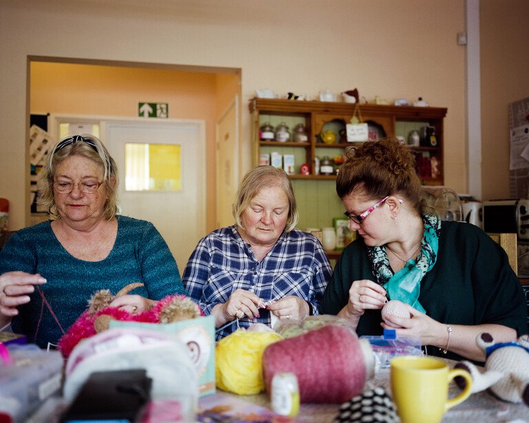 Three women knit together at a community hub in Torbay.