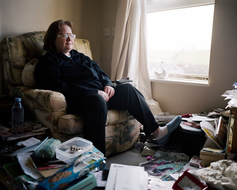 A woman sits in her lounge surrounded by papers and magazines