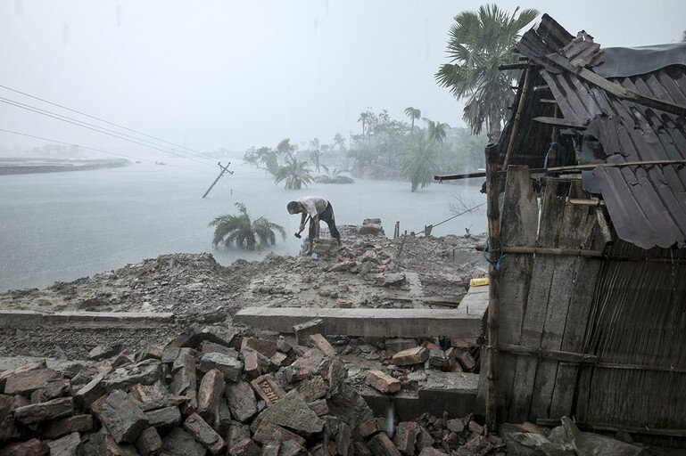 Habibur Rahman Sarder salvages anything still useful from the wreckage of his house, which was hit by a hurricane.