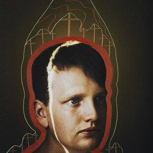 Portrait of a young boy with crosses and a red and green outline around his head and shoulders
