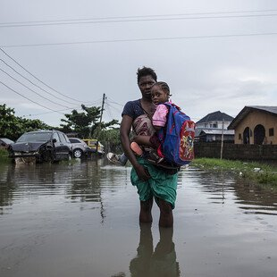 A mother carries her children to school through a flooded street