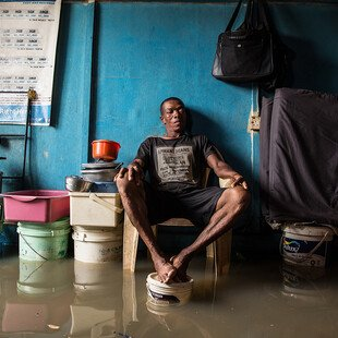 A man sits in his room with his feet up on a paint bucket to avoid the floodwater