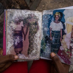 A young girl holds a family album damaged by floodwater