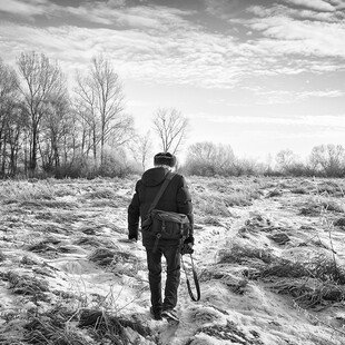 A man walks across a field on a winter's morning with his camera