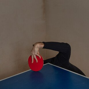 A man holds a table tennis bat in one hand, with the rest of his body hidden under the table