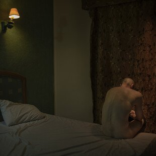 A man sits on a bed naked in a dark hotel room, with his back to the camera