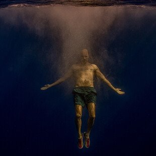 A man swims deep underwater with his arms outstretched