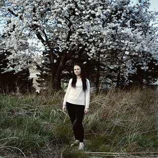 A young woman stands in front of a blossom tree