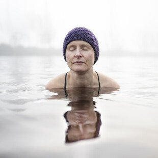 A woman wearing a swimming cap swims in cold water with her eyes closed