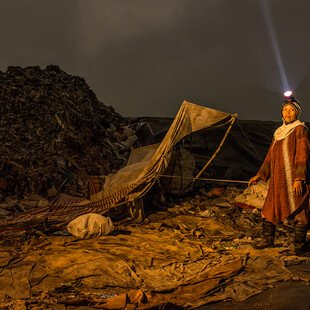 A midwife stands in a landfill site at night, searching for things to sell