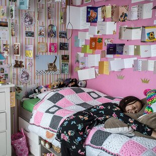 A girl who has been having chemotherapy lays on her bed, surrounded by cards on her walls from the people who love her