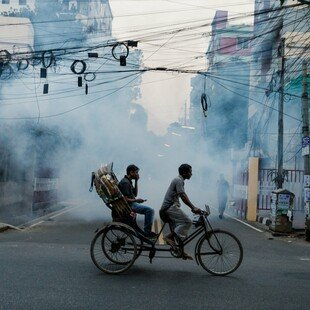 Two people cycling on a street in Uttara which is being sprayed with insecticide to kill mosquitoes