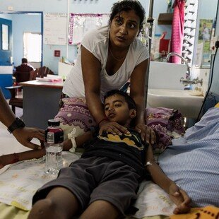 Young boy with dengue lying in a hospital bed