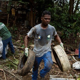 Four men collecting waste and old appliances from a ravine to eliminate mosquito breeding sites