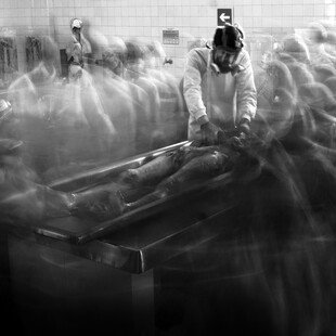 Worker in a morgue, surrounded by ghostly figures