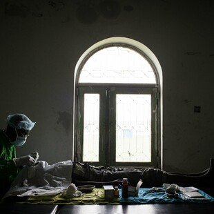 Using only natural light from a window, a trachoma surgeon operates on the eyes of a 13-year-old patient