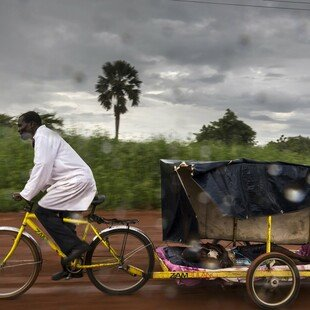 A volunteer community health worker uses his bicycle ambulance to transport a young boy with malaria to the nearest clinic