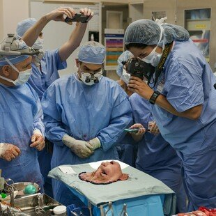 Doctors around a donor's face after it was surgically removed and before transplant