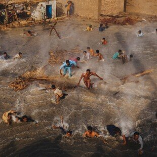 People in a flooded Pakistani village scramble for food rations as they battle the downwash from an army helicopter delivering aid