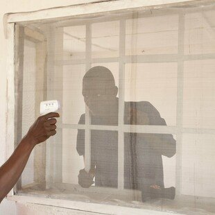 A man suspected of having Ebola has his temperature measured at a clinic run by the NGO Emergency in Sierra Leone