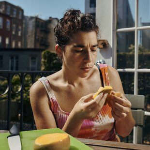 A woman cutting and eating a mango outside on a terrace