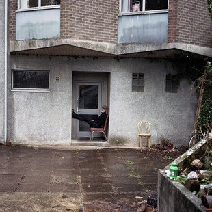 A man sits on a chair in the doorway of his flat.