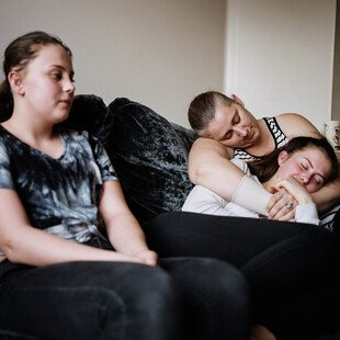 Two teenage girls sit on a sofa with their mother.