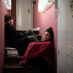 Two women sit on the stairs in their flat.