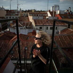 A woman stands atop the roof of her house.