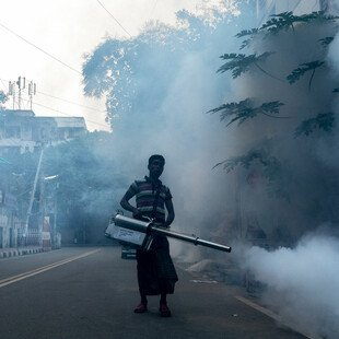 A man sprays the streets of Uttara, a town in the northern suburbs of Dhaka, Bangladesh.
