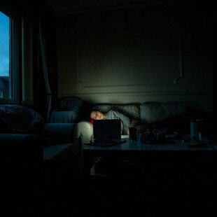 A self-portrait of the photographer laying on a sofa in a dark room watching a laptop.