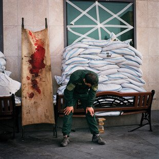 A man weeps beside a bloodied stretcher outside a medical centre.