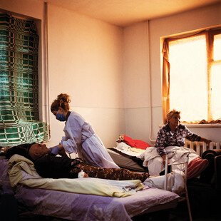 A nurse practitioner tends to a Covid patient in a hospital room.