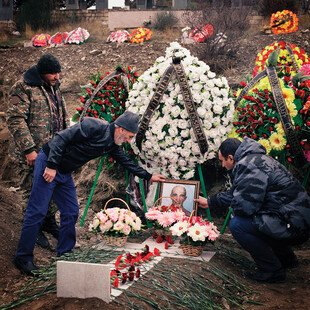 Two men tend a grave covered in flowers.