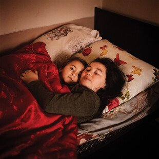 Two girls lying in a bed wrap their arms around each other.