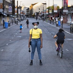 A portrait of a masked pedestrian on London's Ridley Road.