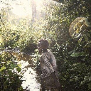 An Mbuti boy runs through the Ituri rainforest.