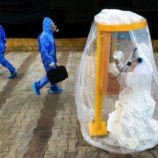A staged image depicting a woman in a wedding dress, calling her groom from inside a protective bubble.