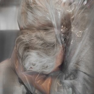 A mother and daughter hug through plastic sheeting, during the Covid-19 pandemic.