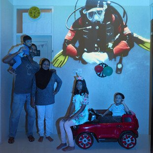 An underwater image is projected behind a family.
