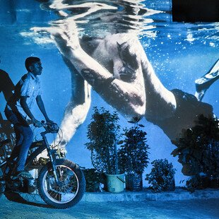 An underwater image is projected behind a man on a motorbike.