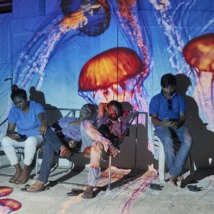 An underwater image is projected behind a group of men.